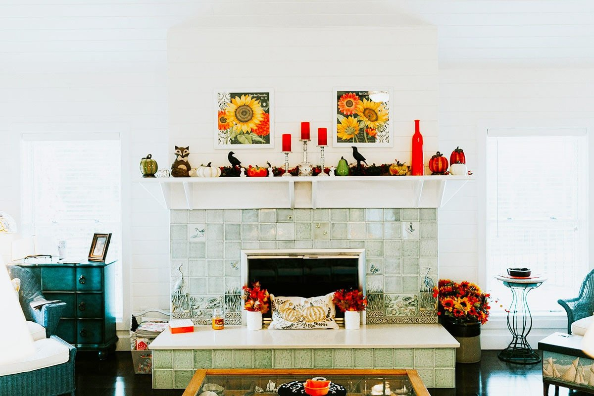 The tiled fireplace is topped with bold candle holders, various decors, and a pair of floral artworks.The tiled fireplace is topped with bold candle holders, various decors, and a pair of floral artworks.