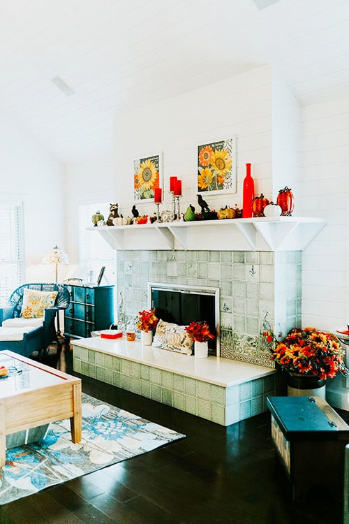 The angled view shows the cozy wicker seat and a wooden coffee table that sits on a floral area rug.
