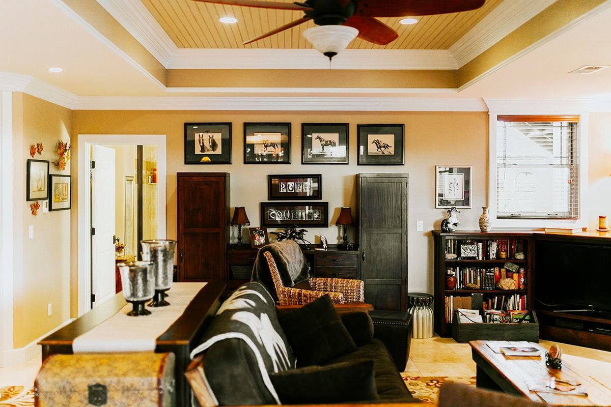 Another living room filled with dark wood furnishings, black-framed artworks, and a tray ceiling mounted with a fan and recessed lights.