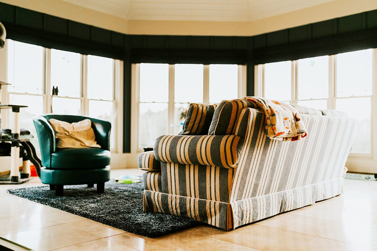 Sitting area with a stripe skirted sofa, a leather round chair, and massive windows that take in incredible views and ample lighting.
