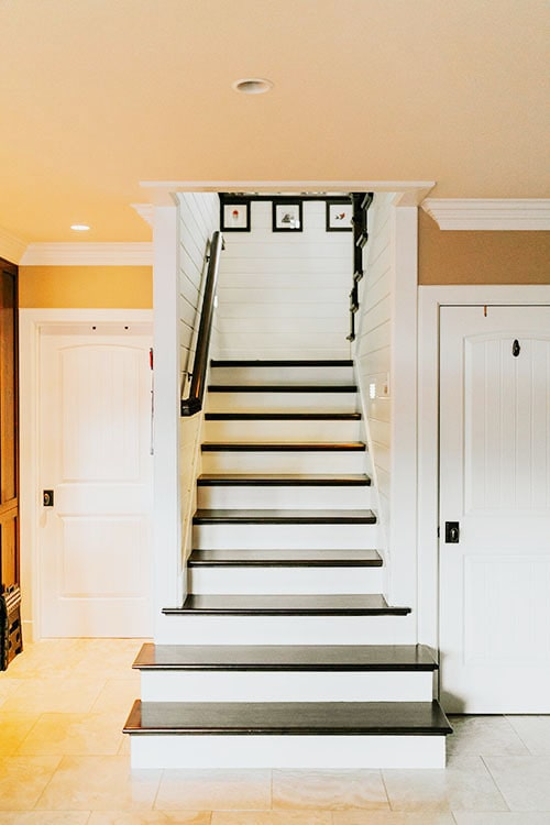 Traditional staircase composed of dark wood treads, white risers, and a black handrail.