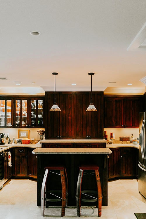 Kitchen with glass front and wooden cabinets, granite countertops, and an island bar lit by a pair of glass dome pendants.