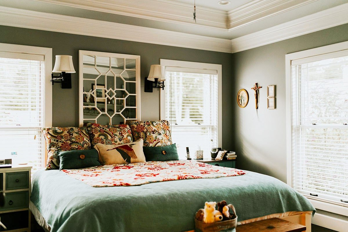 Primary bedroom with a stunning tray ceiling and deep green walls adorned with wooden artworks and a stylish mirror.