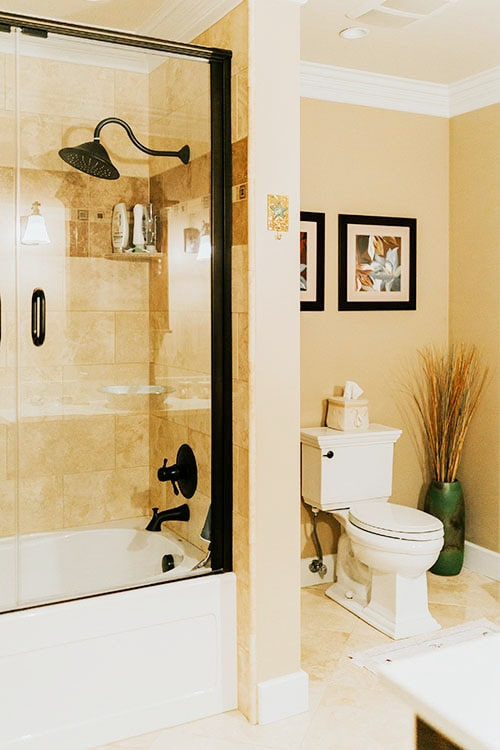 This bathroom is equipped with a toilet and a shower and tub combo fitted with wrought iron fixtures.