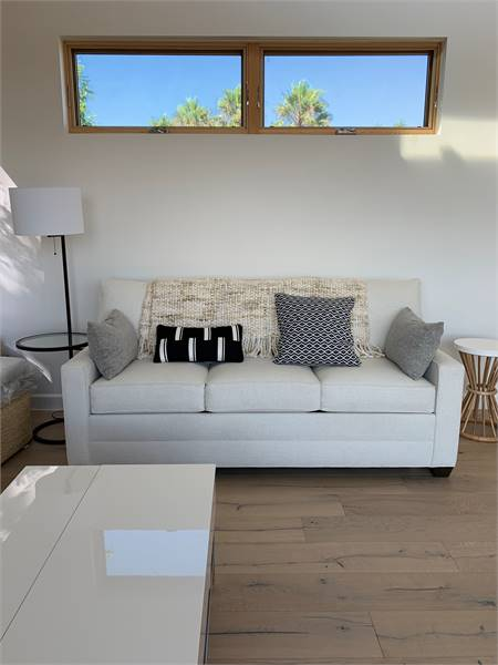 The living room offers a modern coffee table and a light gray sectional flanked by round side tables.