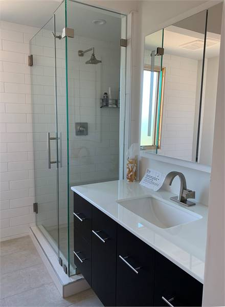 This bathroom offers a walk-in shower and a sink vanity paired with a frameless three-panel mirror.