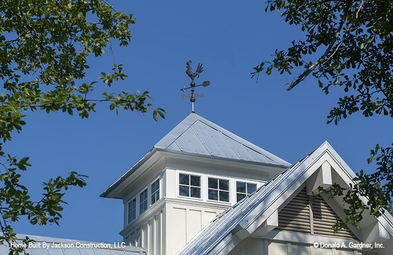 A metal wind vane sits on top of a cupola giving the house a classic look.
