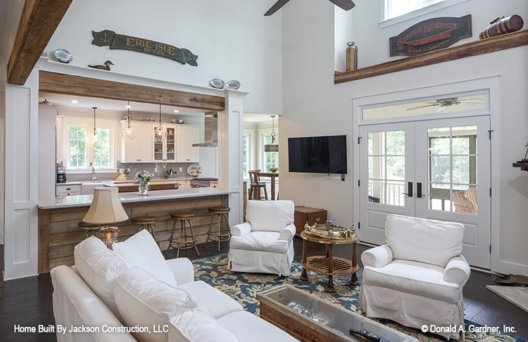 The french door behind the comfy white armchairs leads to the rear screened porch.