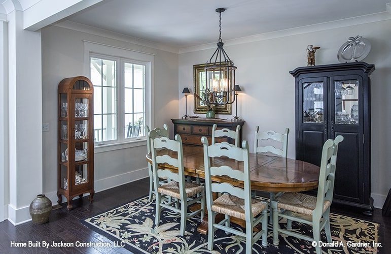 The formal dining room showcases a rustic buffet bar, wooden display cabinets, and oval dining set over a floral rug illuminated with a wrought iron chandelier.