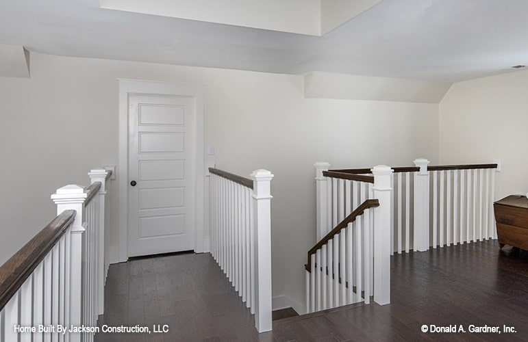 Balcony loft enclosed in white railings with dark wood handrails that match the hardwood flooring.