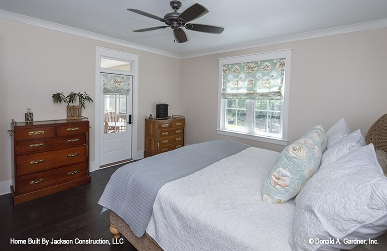 The primary bedroom has wooden furnishings along with glazed windows and door dressed in blue patterned roman shades.