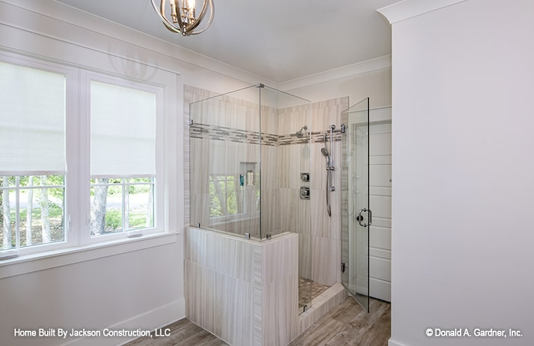 Primary bathroom with a walk-in shower offering chrome fixtures and an inset shelf.