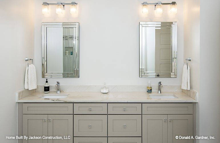 A large dual sink vanity complemented with stainless steel towel holders, sleek mirrors, and warm glass sconces.