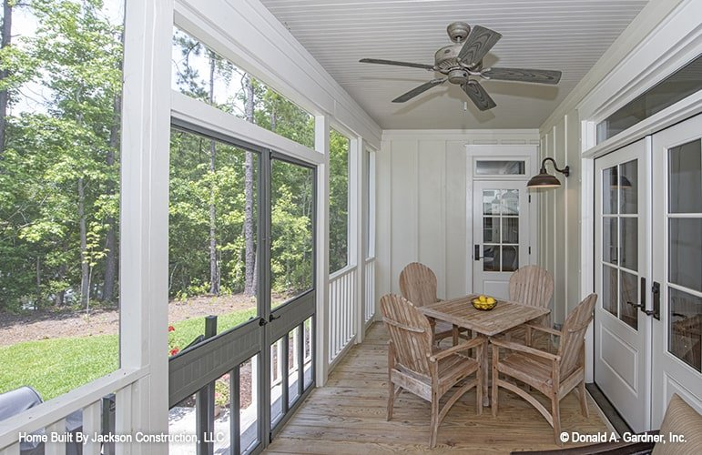 Large french doors, white shiplap ceiling, and natural hardwood flooring complete the screened porch.