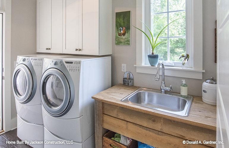 Utility room with white front-load appliances, floating cabinets, and a wooden counter fitted with an undermount sink.