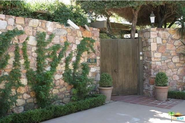The wooden door is flanked by stone walls and green plants. Image courtesy of Toptenrealestatedeals.com.