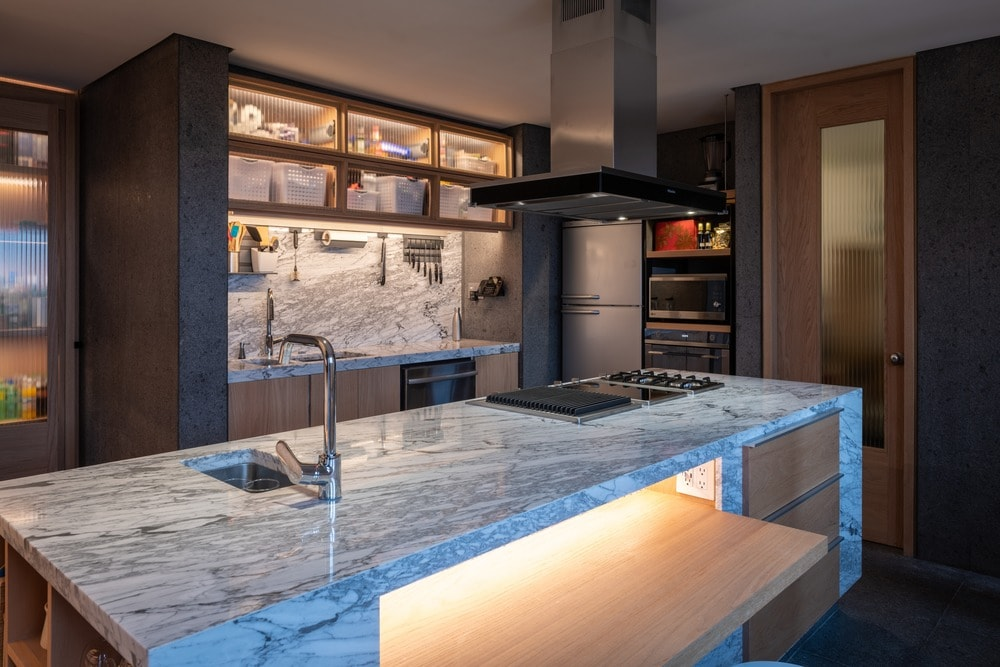 This is the other side of the kitchen island showcasing the white marble countertop that houses the stove topped with a modern vent.