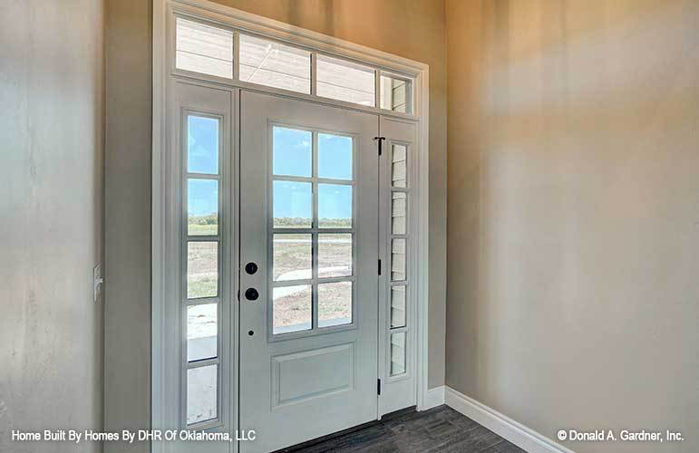 The foyer features a white glazed entry door surrounded with glass panels.