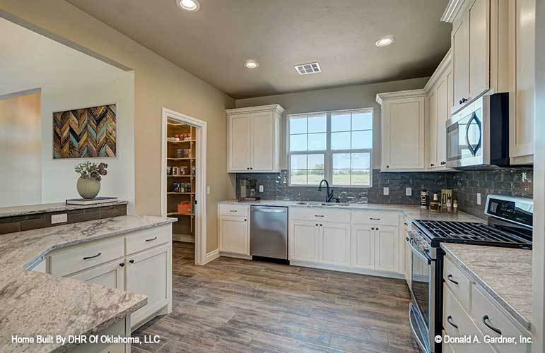 The kitchen is equipped with white cabinetry, stainless steel appliances, granite countertops, and a walk-in pantry.