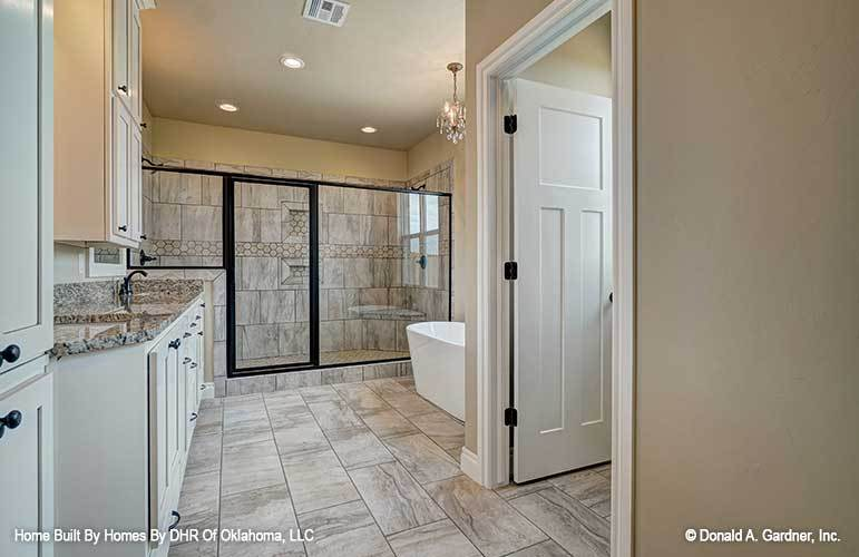 The primary bathroom offers a spacious walk-in shower, an immense vanity, and a freestanding tub illuminated by a crystal chandelier.