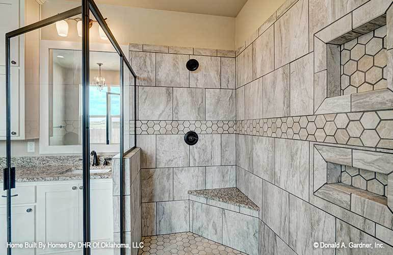 The walk-in shower has hex tile flooring, a corner tiled bench, and inset shelves fitted on the marble-tiled walls.