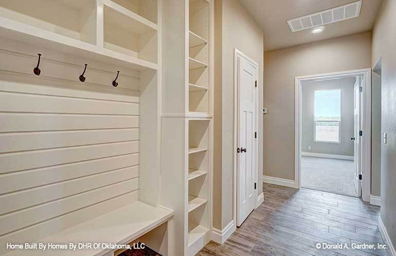 Mudroom with built-in bench and shelves along with coat hooks mounted against the white shiplap walls.