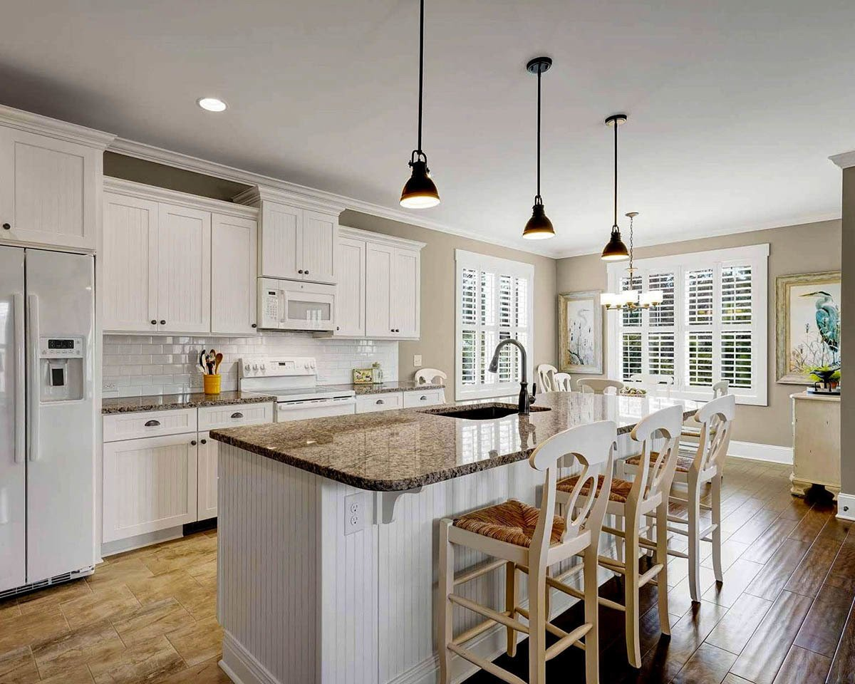 The kitchen offers white appliances and cabinets, granite countertops, and a center island fitted with an undermount sink.