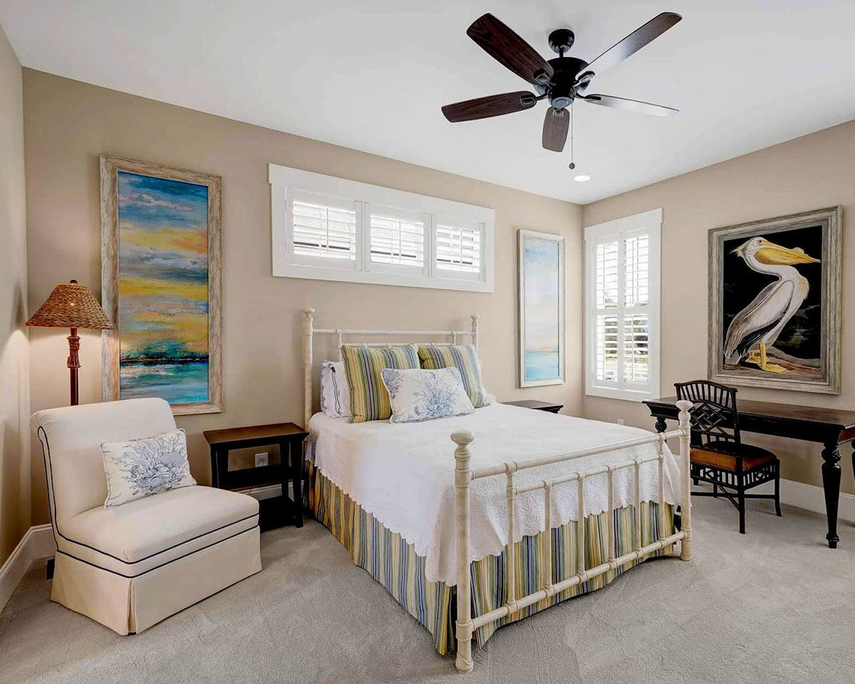 The primary bedroom is furnished with a beige chair, a dark wood desk, and matching nightstands flanking the cozy striped bed.