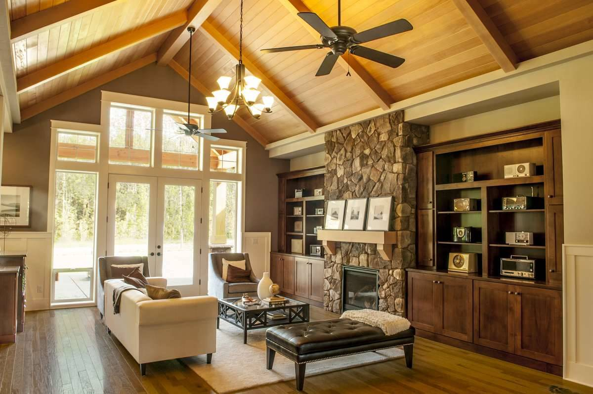 The living room has rich hardwood flooring and a wood-paneled cathedral ceiling mounted with fans and a warm glass chandelier.