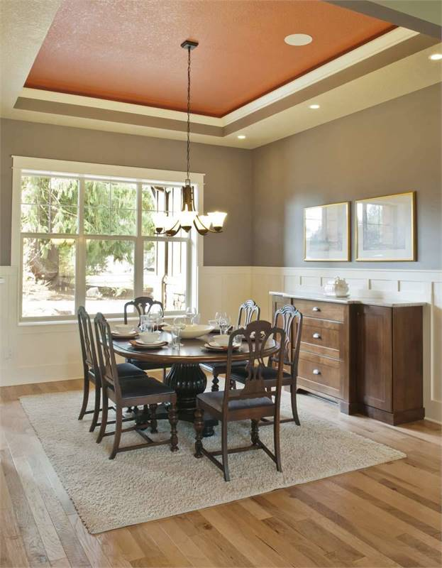 The stunning red tray ceiling adds a pop of color in this formal dining room.