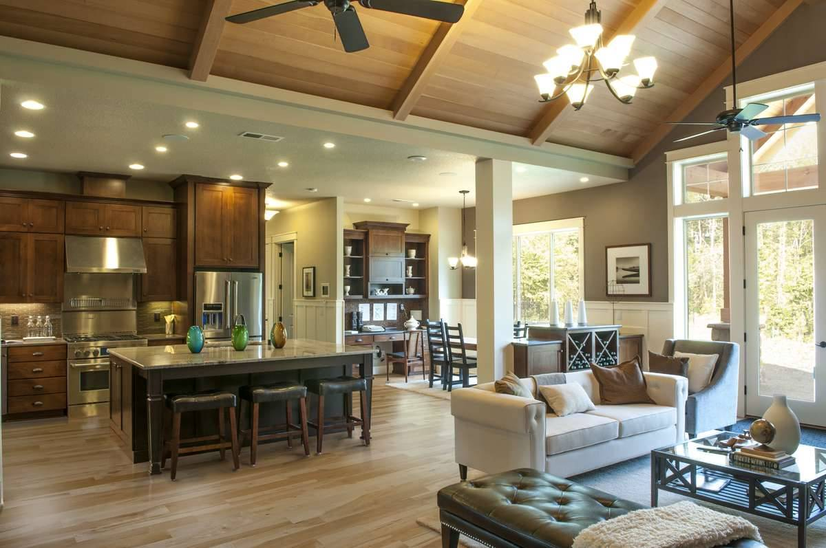 An open layout view showing the living room, breakfast nook, and the kitchen with wooden cabinetry and an immense center island.