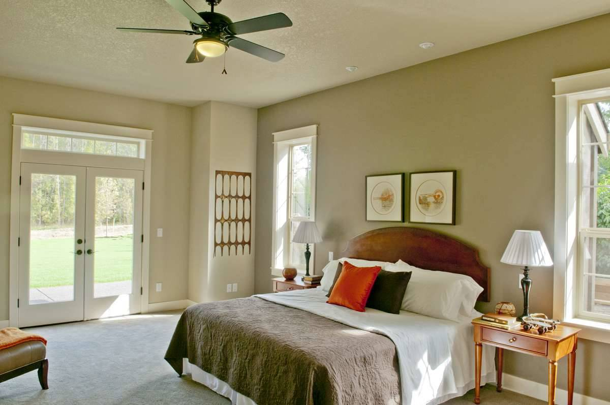 Primary bedroom with beige walls and carpet flooring along with a french door that leads out to the rear porch.