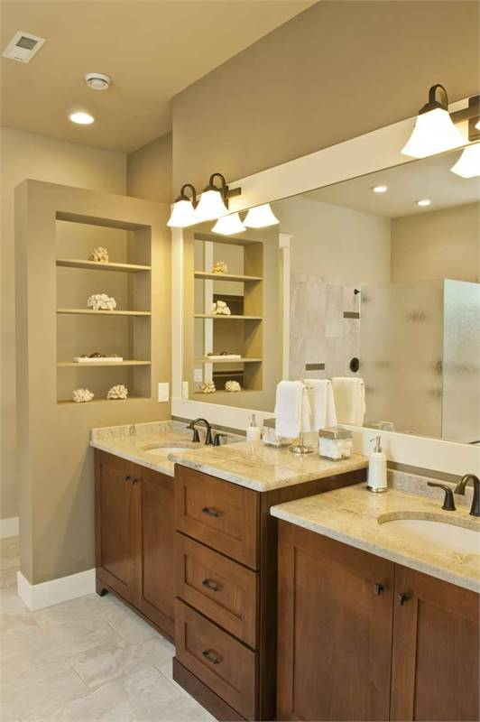 The primary bathroom offers a dual sink vanity paired with a large white-framed mirror.