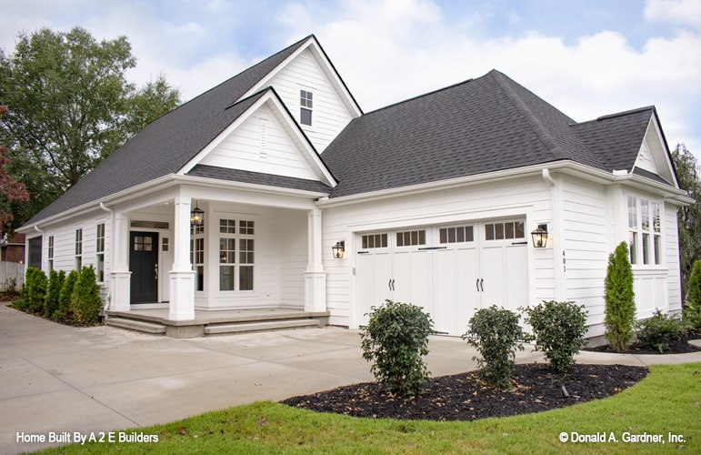 The home's angled front view showing the covered front porch and the side-entry garage illuminated by outdoor sconces.