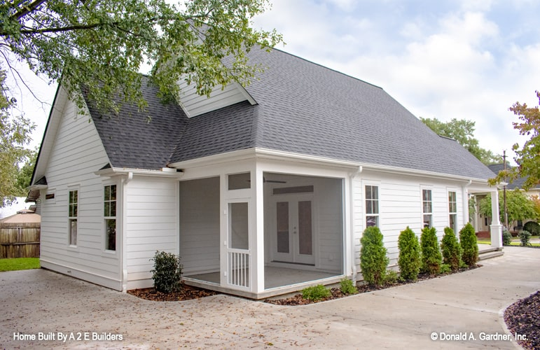 Rear view with white exterior siding, framed windows, and a french door that opens to the screened porch.