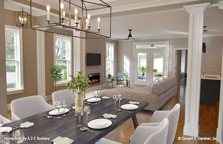 The dining area offers modern upholstered chairs and a rectangular table under the candle chandelier.