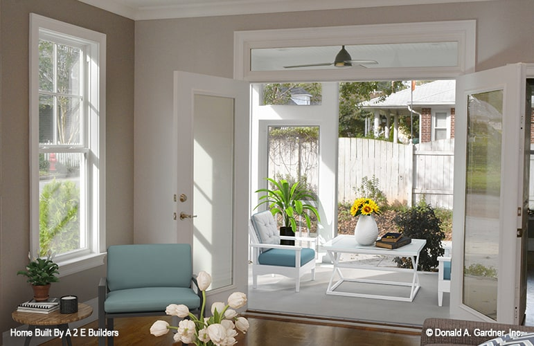 A french door from the living room opens to the rear porch filled with cushioned chairs and a white table.