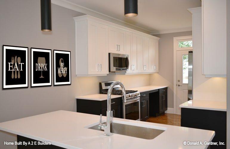 Kitchen equipped with stainless steel appliances, contrasting white and black cabinets, and a granite top island bar.