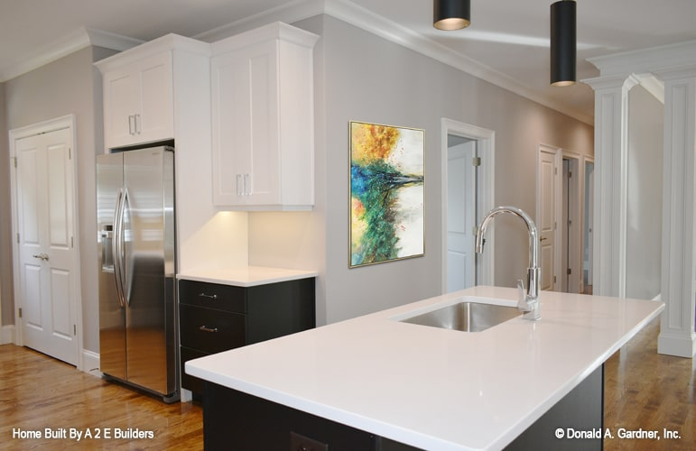 The center island is fitted with an undermount sink and a gooseneck faucet.