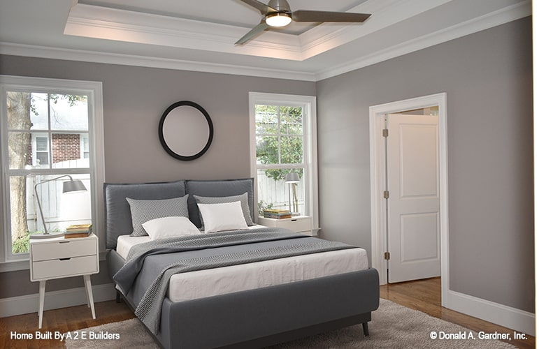 Primary bedroom showcasing gray walls, hardwood flooring, and a tray ceiling mounted with a fan.