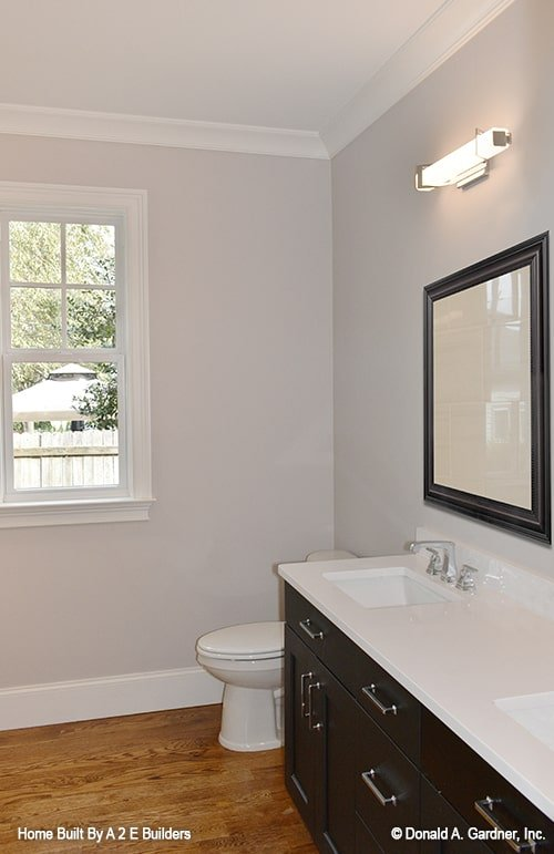 Primary bathroom with a toilet and a dual sink vanity well-lit by linear sconces.