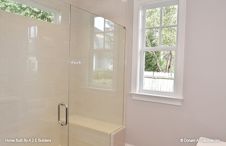 There's also a walk-in shower with a tiled bench and frameless glass enclosure.