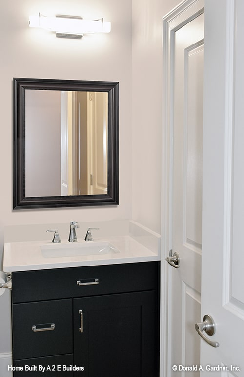 The powder room features a black vanity complemented with a framed mirror and a bright glass sconce.