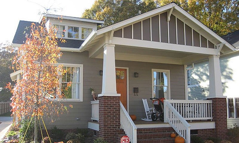 Home's front view showing the gray exterior siding, a gable dormer, and a covered porch lined with tapered columns.
