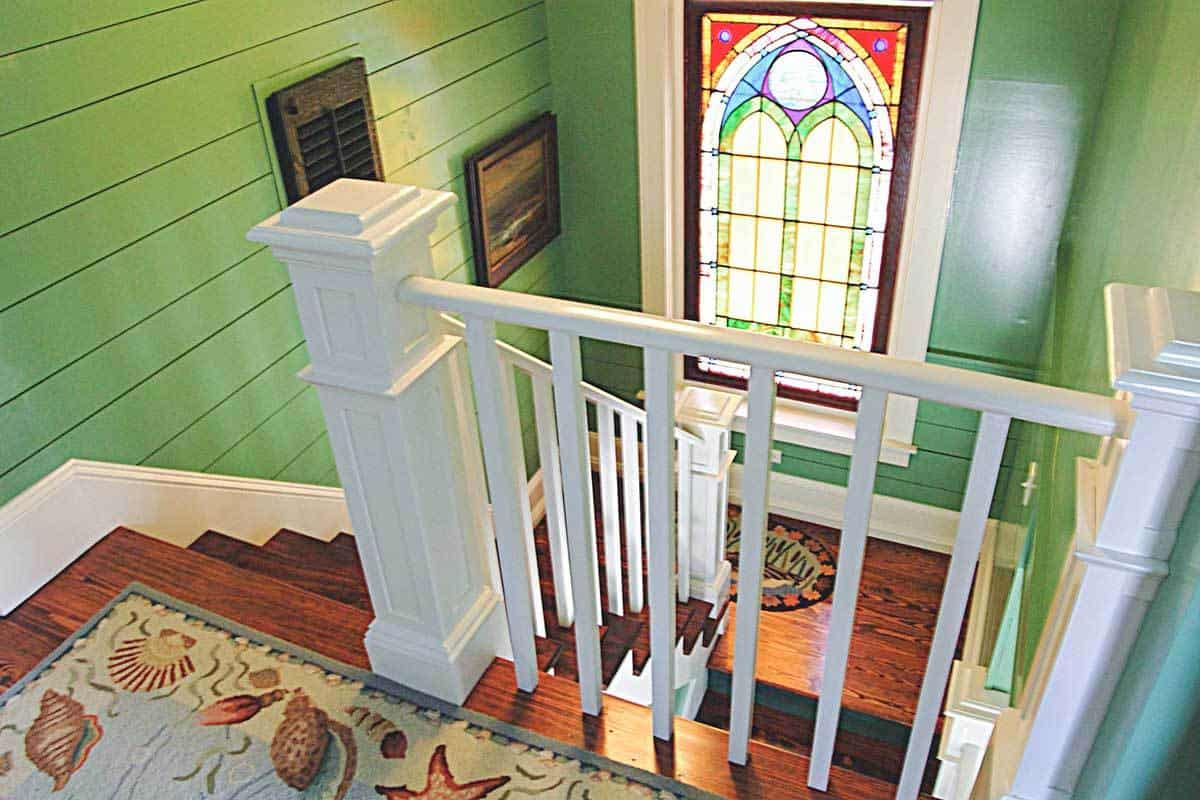 View of the staircase landing from the second floor boasting a stained glass window that lets natural light in.