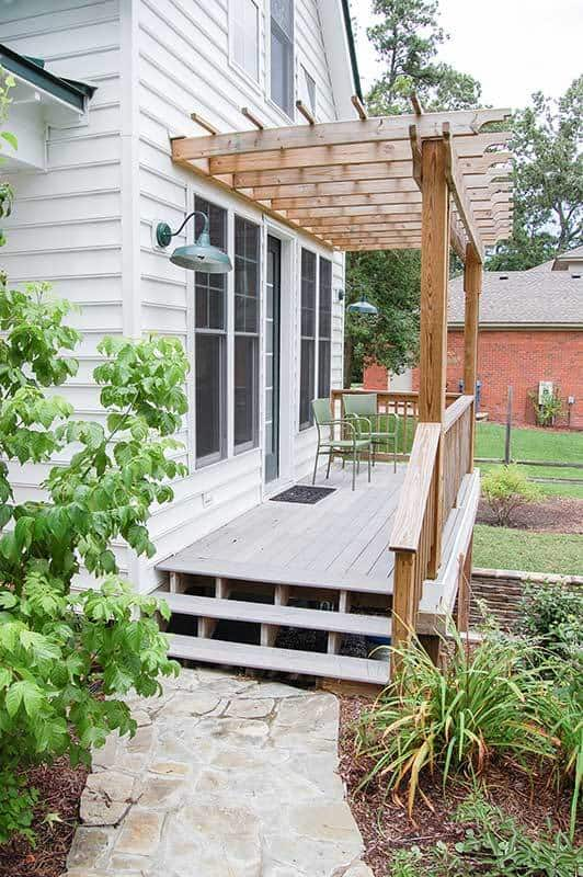 The side porch is enclosed in a decorative pergola fixed against the white exterior siding.