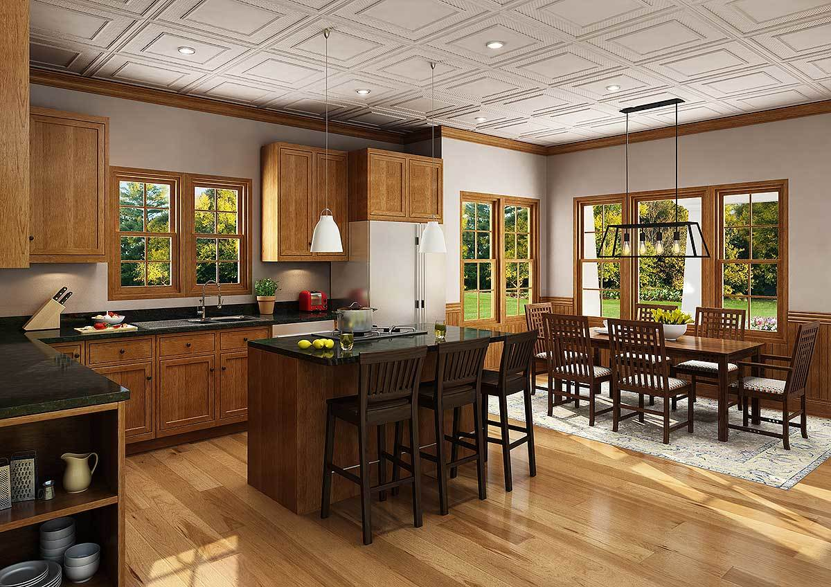 An eat-in kitchen showcasing a rectangular dining set over the bordered area rug along with wooden cabinets that match the center island.