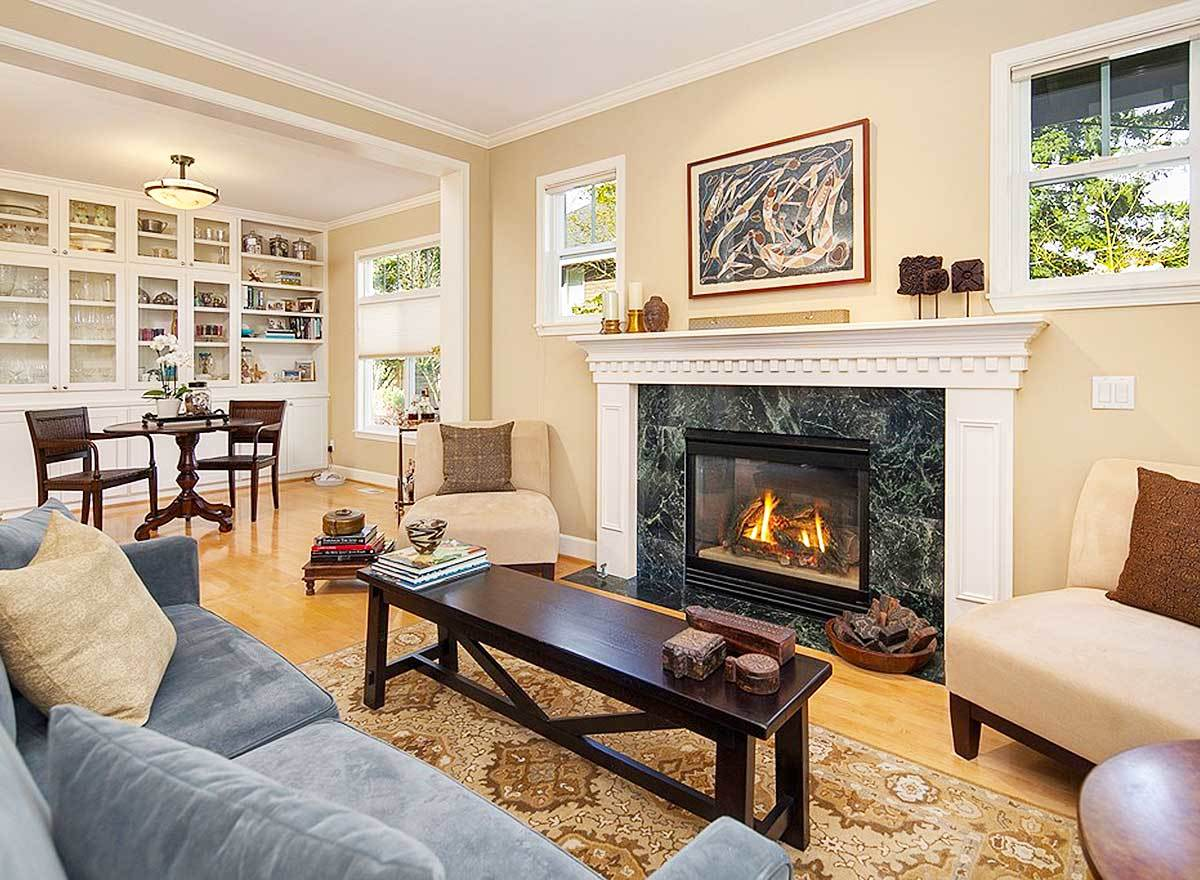 Family room with a velvet gray sofa, beige chairs, a marble fireplace, and a wooden bench that doubles as a coffee table.