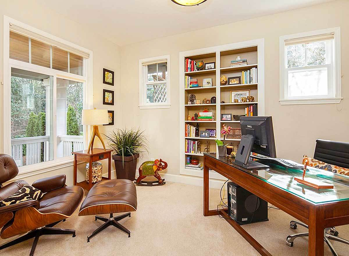 The study has a glass top desk, an inset bookcase, and a brown leather lounger paired with a matching ottoman.