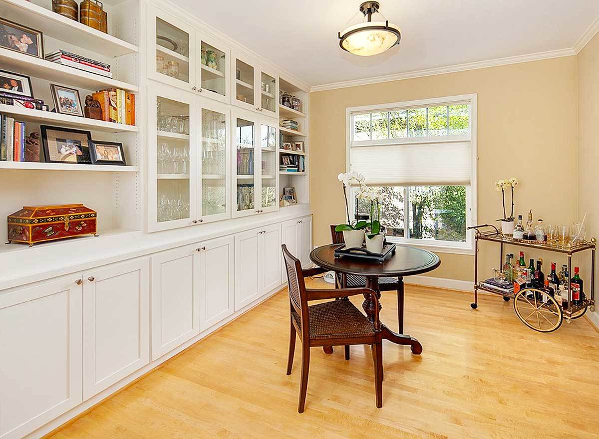 The breakfast nook offers a mobile kitchen shelf, round wooden table and chairs, and a large white cabinet filled with various decors and books.